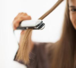 Closeup on woman straightening hair with straightener