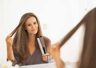 Happy young woman checking hair after straightening