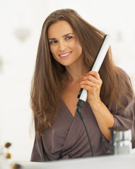 Young woman curling hair with straightener