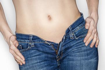 ventre bassin et hanches de femme en jean braguette ouverte