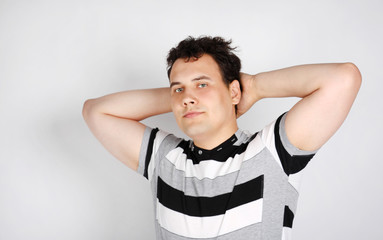 Brunet man in striped T-shirt smiles and stretches oneself on gr