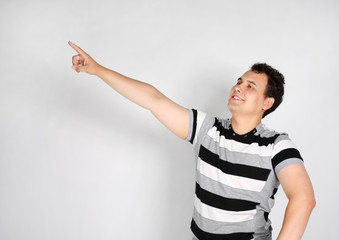 Brunet man in striped T-shirt smiles and points to side on grey
