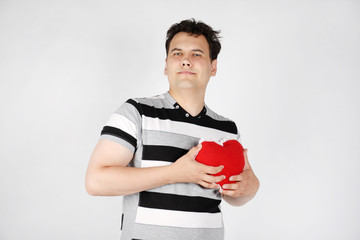 Suffering handsome man holds red soft heart on grey background.