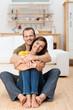 glückliches paar sitzt zuhause auf dem boden