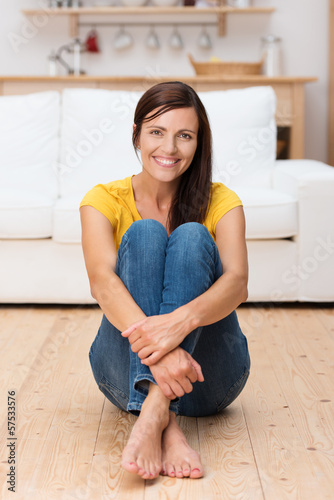 entspannte frau sitzt zu hause auf dem fußboden