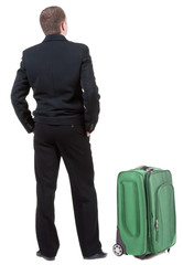 back view of adult man in black suit  traveling with suitcas .