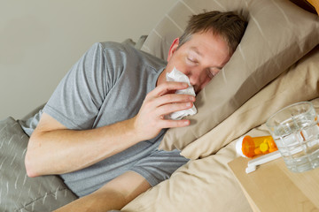Mature Man wipiung Nose while lying in bed