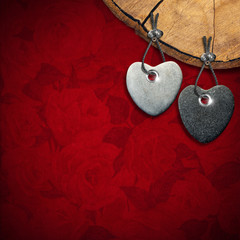 Two Stone Hearts on Red Floral Background