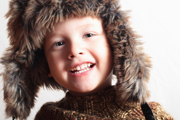 funny smiling child in fur hat.fashion.winter style.little boy