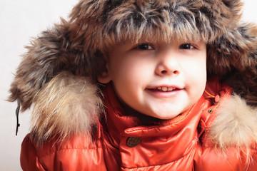 child in fur hat and orange winter jacket. fashion kid.children