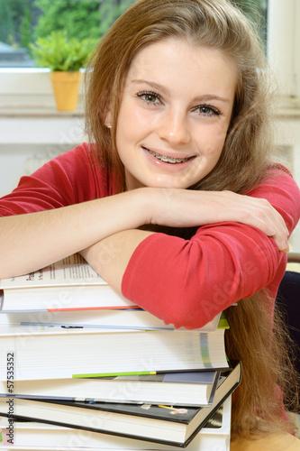 Freundliche Schülerin mit vielen Büchern