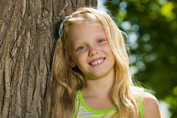 Young blonde girl near a tree
