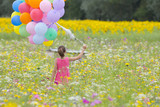 Girl carrying bunch of balloons among wildflowers in sunny meadow