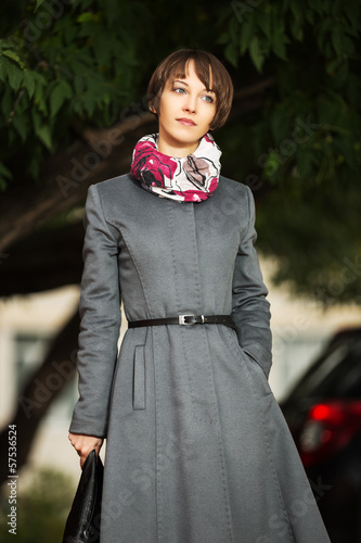 Young woman in grey classic coat with a handbag