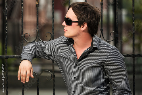 Young man at the cast iron fence