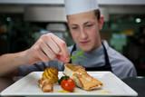 Koch garniert ein Gericht