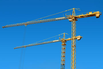 Tower cranes on a blue sky background