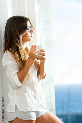 Teen girl with coffee mug at window.