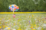 Smiling girl running with bunch of balloons among wildflowers in sunny meadow