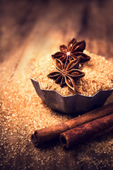 Cinnamon sticks and star anise on brown  sugar on wooden backgro