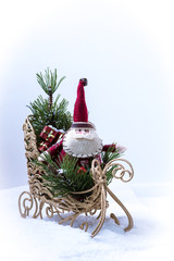 Miniature Santa Claus on a sleigh with gifts.