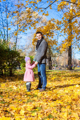 Young father and little girl enjoy vacation in autumn park