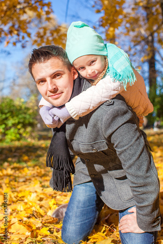 Adorable little girl with happy father having fun in autumn park