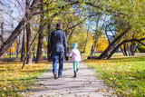 Rear view of young father and little girl walking in autumn park