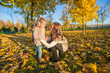 Little adorable girl and young mother in autumn park on sunny
