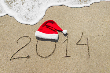 happy new year 2014 with christmas hat on sandy beach - holiday
