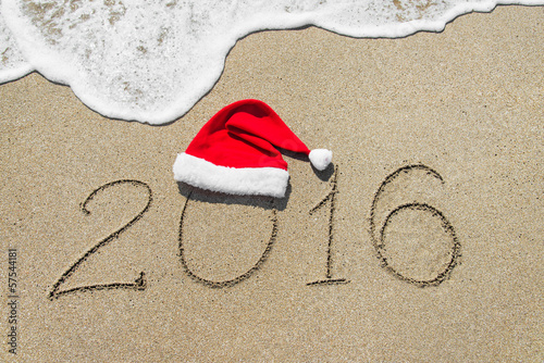 happy new year 2016 with christmas hat on sandy beach - holiday