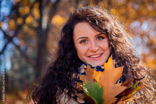 Girl with bunch of leaves in the autumn park
