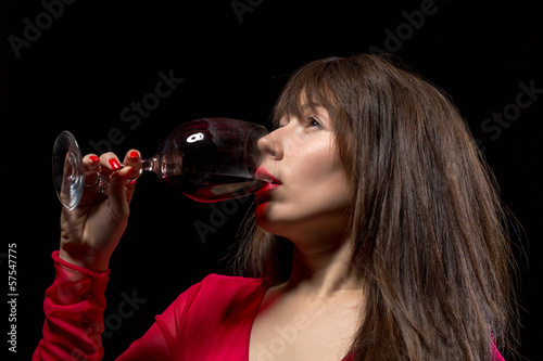Young woman drinking red wine from a glass