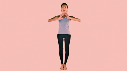 young woman practices yoga moves in studio