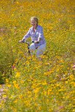 Smiling woman riding bicycle among wildflowers in sunny meadow
