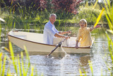 Portrait of smiling couple in rowboat on lake