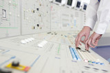 Engineer pushing buttons on panel in control room of nuclear power station