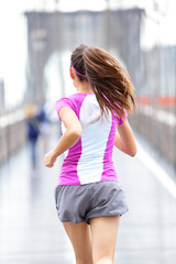 City runner - woman running on Brooklyn Bridge
