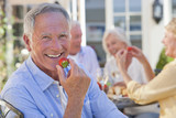 Portrait of smiling senior man eating strawberry on patio with friends enjoying wine and lunch in background
