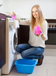 woman using washing machine with laundry detergent