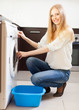 Cheerful long-haired woman doing laundry