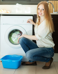 Blonde long-haired woman using washing machine at home
