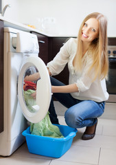 Home laundry. Happy blonde woman  the washing machine