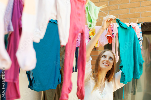 Long-haired housewife hanging clothes to dry