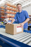 Portrait of worker with cardboard box on production line in distribution warehouse