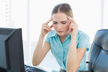 Classy grimacing businesswoman having a headache