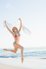Cheerful slender woman jumping in the air holding shawl