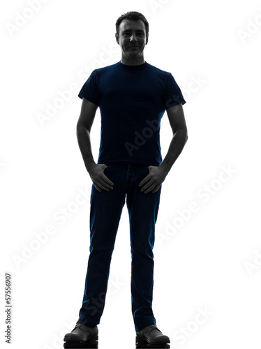 man standing smiling with thumbs in pockets silhouette