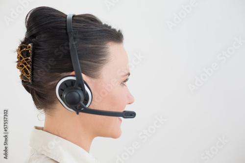 Side view of a beautiful businesswoman using headset