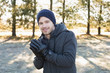 Smiling man in warm clothing shivering while having a walk in fo